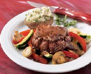 Beef medaillons on a bed of vegetables with red wine sauce